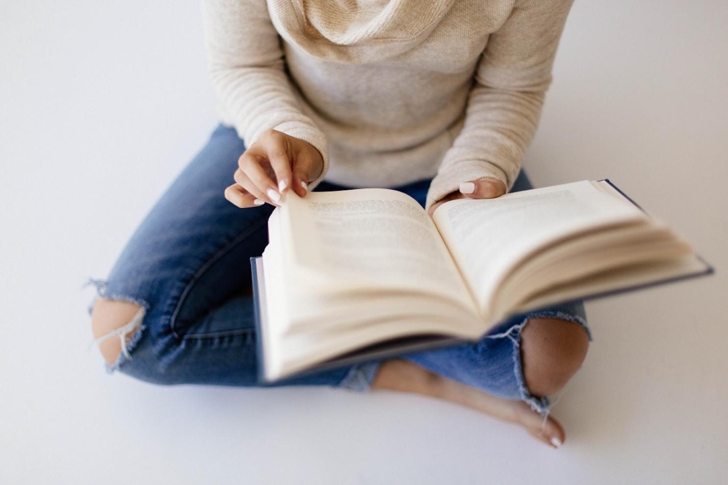 Woman sitting on floor reading book
