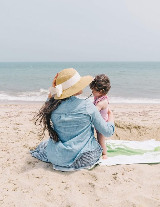 Mother in chambray shirt sitting on beach with toddler girl