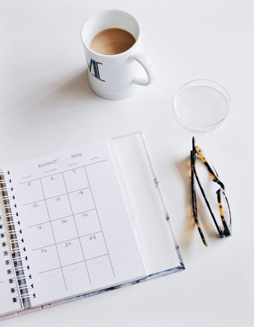 A monthly planner with cup of coffee and reading glasses