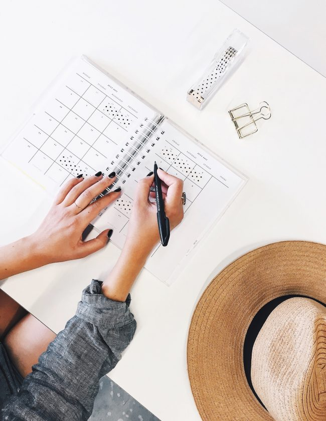 Young woman writing in monthly planner